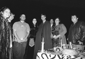 Participants in the Pagan Student Union celebration of Samhain gather in the Oval on Monday night behind a table holding items used in their ceremony.